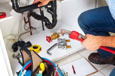 Houston Plumber Kneeling to Fix the Bathroom Pipes with His Tools