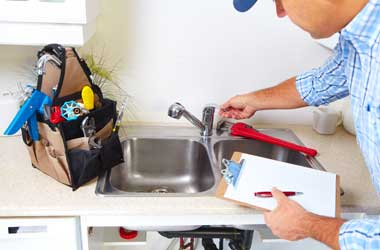 Plumber Inspecting a Kitchen Faucet in Houston