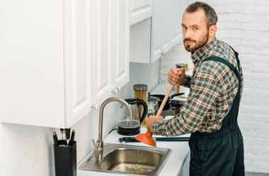 Plumber Unclogging a Kitchen Sink Drain in Houston
