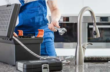 Plumber Removing Tools From His Tool Box to Fix Kitchen Sink in Houston