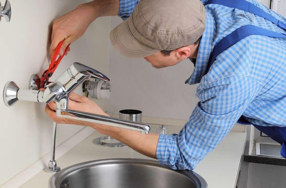 man installing new faucet